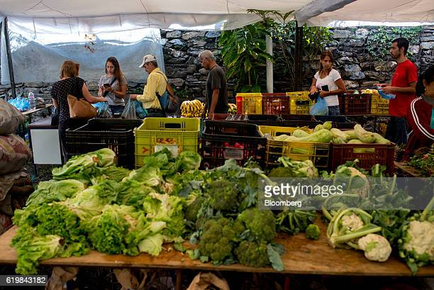 Customers stand in line at a street market in Caracas Venezuela on Monday Oct 17 2016 Once one of the world's strongest currencies the bolivar has...