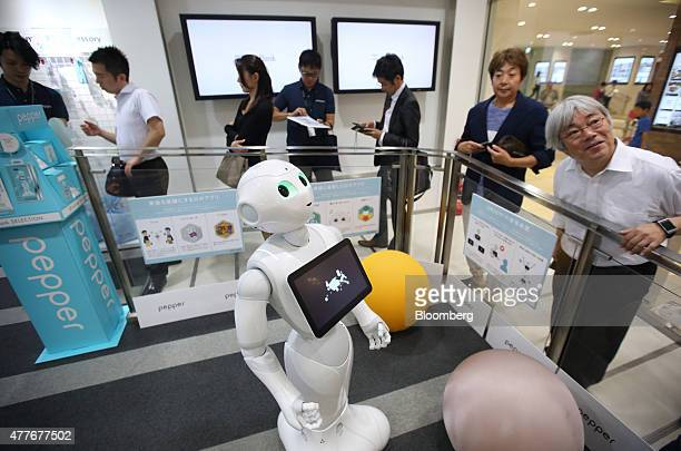 Customers stand in line behind SoftBank Corp's humanoid robot Pepper as they wait to preorder the robot inside the company's store in Tokyo Japan on...
