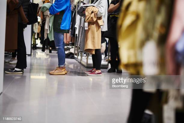 Customers stand in line to purchase clothing at a Zara fashion store operated by Inditex SA in the Westfield Garden State Plaza mall on Black Friday...