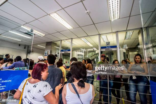 Customers stand in line to speak to an employee about withdrawing money from the Workers Severance Fund inside a Caixa Economica Federal bank branch...