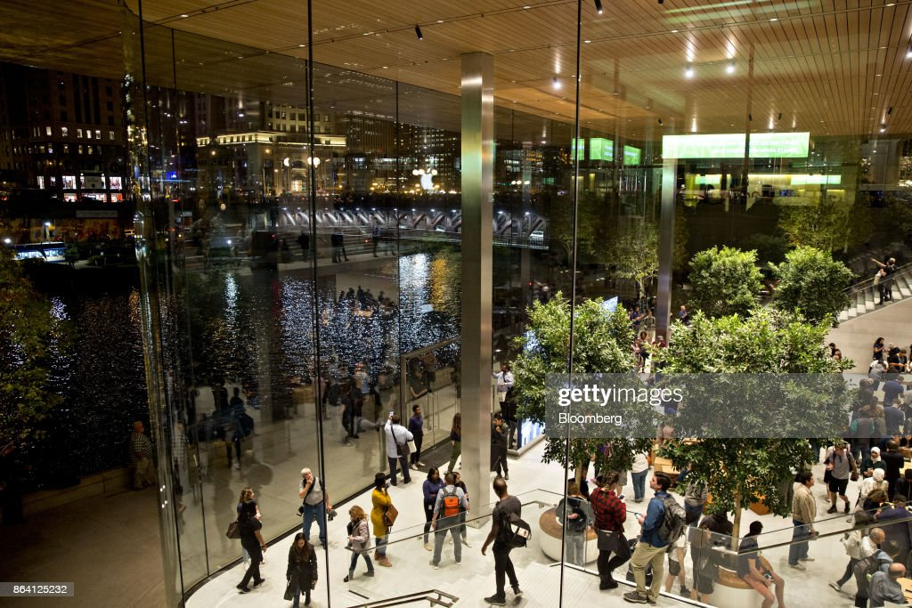 Customers stand inside the new Apple Inc. Michigan Avenue store in Chicago, Illinois, U.S., on Friday, Oct. 20, 2017. The building features exterior walls made entirely of glass with four interior columns supporting a 111-by-98 foot carbon-fiber roof, designed to minimize the boundary between the city and the Chicago River. Photographer: Daniel Acker/Bloomberg via Getty Images