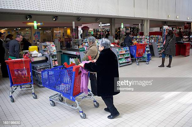 Customers stand with their purchases loaded in shopping carts as they queue at checkout counters inside a Carrefour SA supermarket in Portet sur...