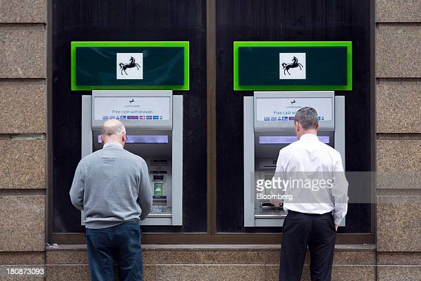 Customers stop to use automated teller machines outside a Lloyds bank branch operated by the Lloyds Banking Group Plc in London UK on Tuesday Sept 17...