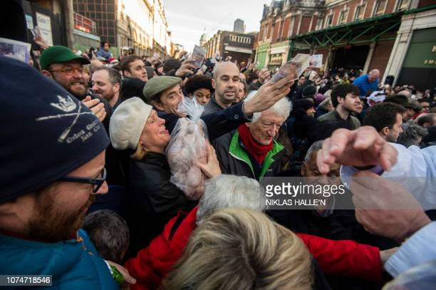 Customers stretch for cuts of meat during the traditional preChristmas meat auction at Smithfield market in the city of London on December 24 2018