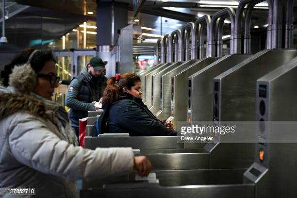 Customers swipe their metro cards as they move through the turnstiles at the Fulton Center subway station, February 27, 2019 in New York City. On...