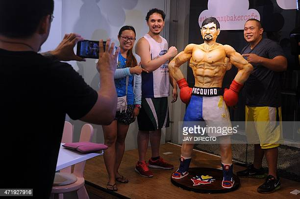 Customers take a picture with a life size 70 kilogram cake worth 4000 USD of Philippine boxing icon Manny Pacquiao at a cafe in Manila on May 2 2015...