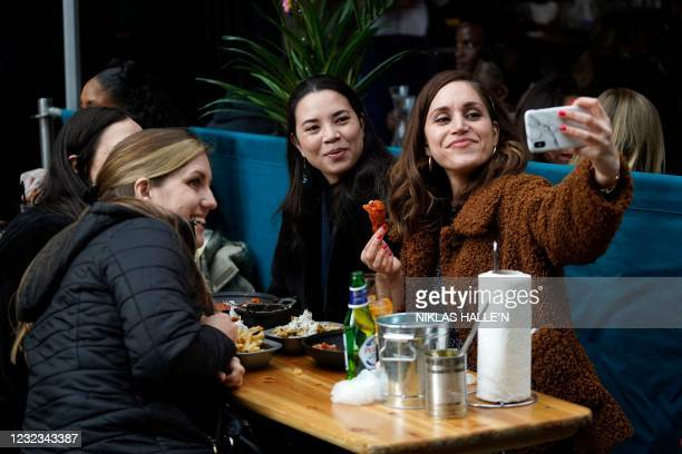 Customers take a 'selfie' photograph as they eat and drink at an outside table in the Soho area of London, on April 16, 2021 following step two of...