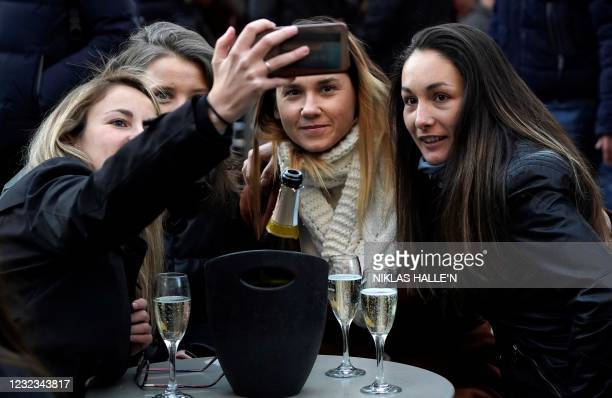 Customers take a 'selfie' photograph with their drinks at an outside table in the Soho area of London, on April 16, 2021 following step two of the...