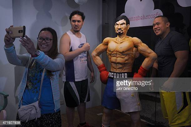 Customers take a selfie with a life size 70 kilogram cake worth 4000 USD of Philippine boxing icon Manny Pacquiao at a cafe in Manila on May 2 2015...