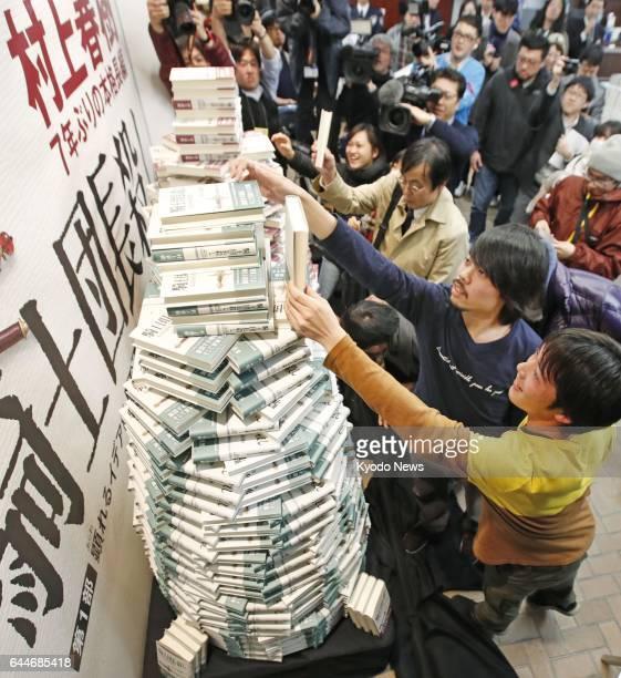Customers take copies from a pile of Haruki Murakami's first multivolume novel in seven years 'Kishidancho Goroshi' at a Tokyo bookstore at midnight...