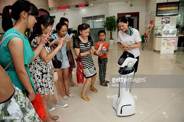 Customers take photos of an intelligent robot at hall of Sichuan Neijiang Branch Agriculture Bank of China on July 7 2016 in Neijiang Sichuan...