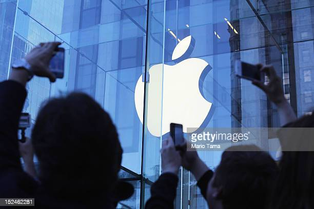 Customers take photos while waiting on line to purchase the Apple iPhone 5 outside the Apple Fifth Avenue flagship store on the first morning it went...