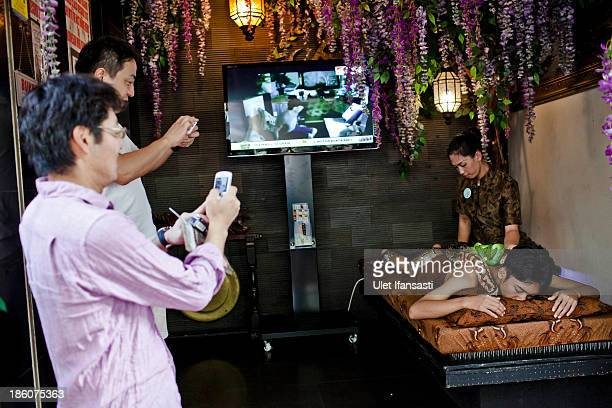 Customers take pictures as staff members perform a massage with pythons at at Bali Heritage Reflexology and Spa on October 27 2013 in Jakarta...