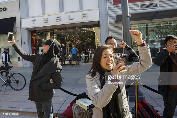 Customers take selfie photographs while waiting in line ahead of the Model 3 announcement outside the Tesla Motors Inc store on the Third Street...
