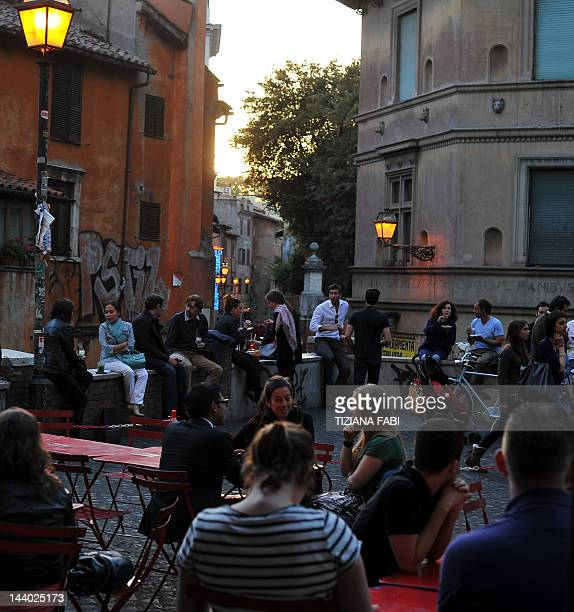 Customers take the aperitif at a bar terrace in Rome on April 27 2012 Many Italian bars offer an 'Aperitivo' with an all you can eat buffet instead...