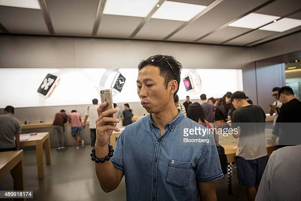 A customers takes a photograph using an Apple Inc's iPhone at the company's store during the sales launch of the iPhone 6s and iPhone 6s Plus at the...