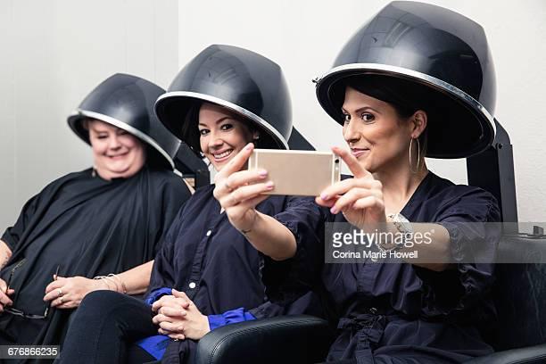 Customers taking selfie under hair dryers