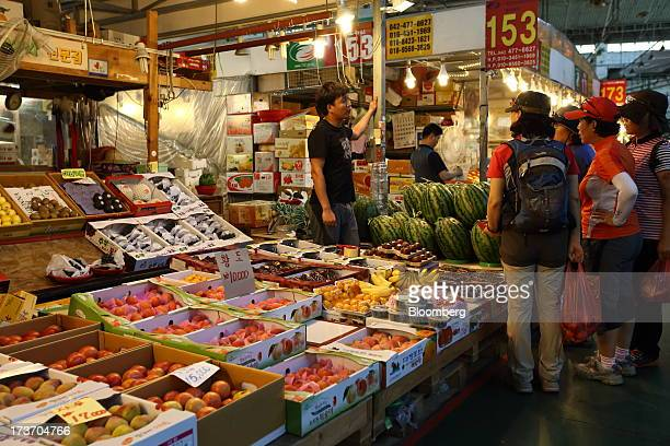 Customers talk to a fruit vendor at Noeun Agricultural and Marine Products Wholesale Market in Daejeon, South Korea, on Tuesday, July 16, 2013. South...
