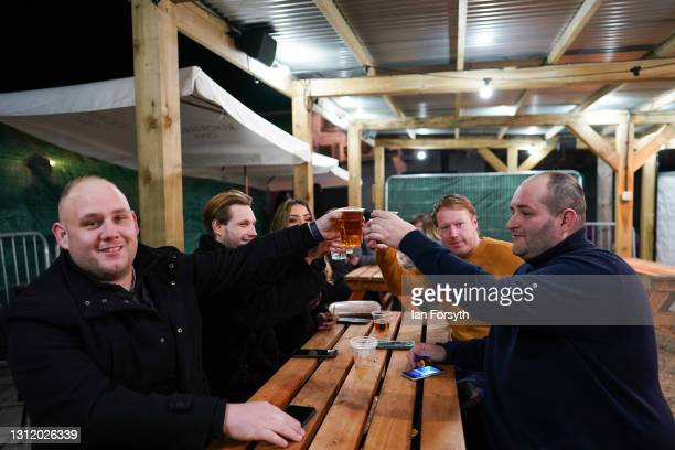 Customers toast as they enjoy a drink at the Switch bar in Newcastle shortly after midnight following the easing of lockdown measures on April 12,...