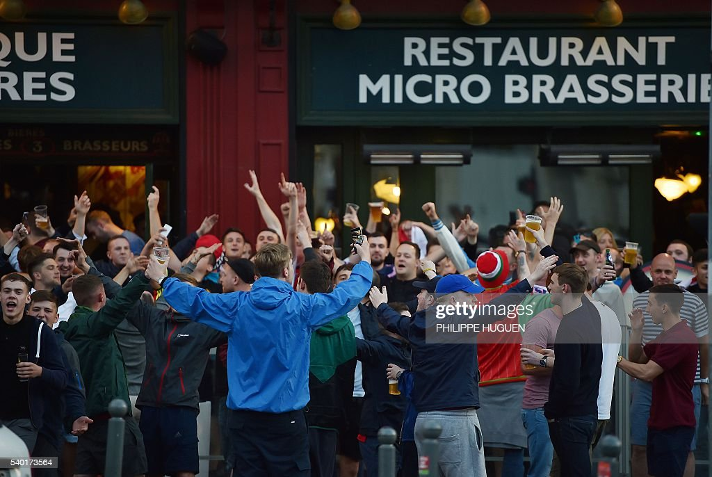 Customers, tourists and footbal fans drink beer at the terrace of a bar in Lille, northern France, on June 14, 2016. The bars in downtown Lille will be closed 'at midnight' on June 15 and 16, on the sidelines of the Euro 2016 football tournament matches Russia vs Slovakia in Lille and England vs Wales in Lens, has announced on June 14, 2016 the Prefect of the Nord region, Michel Laland. / AFP / PHILIPPE