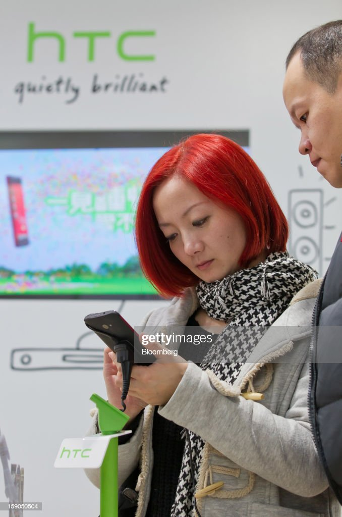 Customers try out an HTC Corp. Butterfly smartphone at one of the company's stores in Taipei, Taiwan, on Sunday, Jan. 6, 2013. HTC is scheduled to release fourth-quarter earnings on Jan. 7. Photographer: Maurice Tsai/Bloomberg via Getty Images