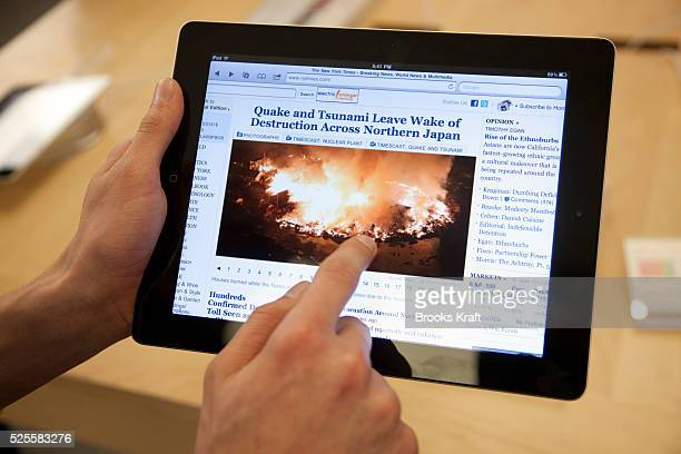 Customers try out the new Apple iPad 2 tablet at an Apple Store in Bethesda MD displaying images of the earthquake in Japan