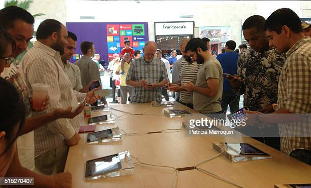 Customers try out the new iPhone 6 models inside the Apple Store while others wait outside in line to purchase the cellphones at Westfield Topanga...