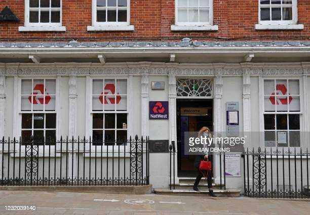 Customers use a NatWest bank on the High Street in Winchester, south west England on March 31, 2021.