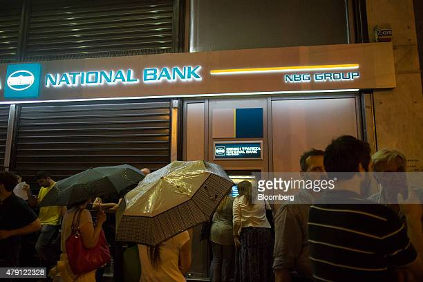 Customers use an automated teller machine as pedestrians shelter from the rain beneath umbrellas outside a National Bank of Greece SA bank branch...