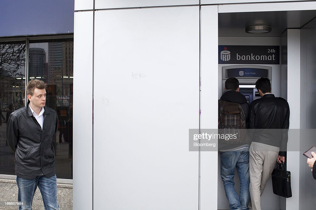Customers use an automated teller machine (ATM) operated by PKO Bank Polski SA in Warsaw, Poland, on Thursday, April 11, 2013. Poland's central bank kept interest rates unchanged at a record-low 3.25 percent yesterday. Photographer: Bartek Sadowski/Bloomerg