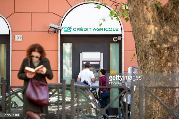 Customers use an automatic teller machine at a branch of Credit Agricole SA's Cariparma bank in Rome, Italy, on Tuesday, May 2, 2017. Cariparma, is...