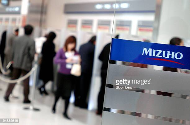 Customers use ATM machines at a Mizuho bank branch in Tokyo Japan Friday December 9 2005 Mizuho Financial Group Inc Japan's secondbiggest bank said a...
