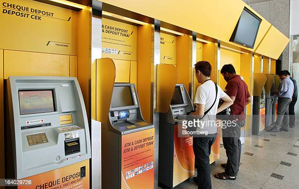 Customers use automated teller machines and cash deposit machines at a Maybank Islamic Bhd branch at the company's headquarters in Kuala Lumpur...