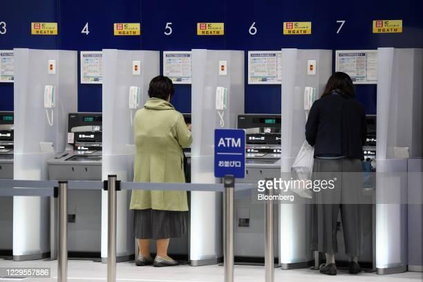 Customers use automated teller machines at a branch of Mizuho Bank Ltd. In Kawasaki, Kanagawa Prefecture, Japan, on Monday, Nov. 9, 2020. Japanese...