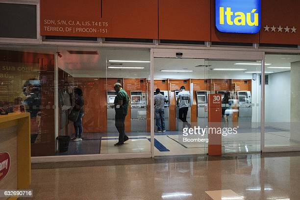 Customers use automated teller machines at a Itau Unibanco Holding SA bank branch in Brasilia Brazil on Wednesday Jan 18 2017 Itau the biggest bank...