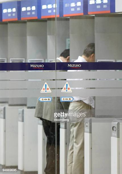 Customers use automated teller machines at a Mizuho Bank Ltd branch in Tokyo Japan on Wednesday Nov 14 2007 Mizuho Financial Group Inc Japan's...