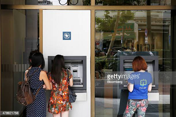 Customers use automated teller machines at an Alpha Bank AE bank branch in Athens Greece on Friday June 26 2015 Greek Prime Minister Alexis Tsipras...