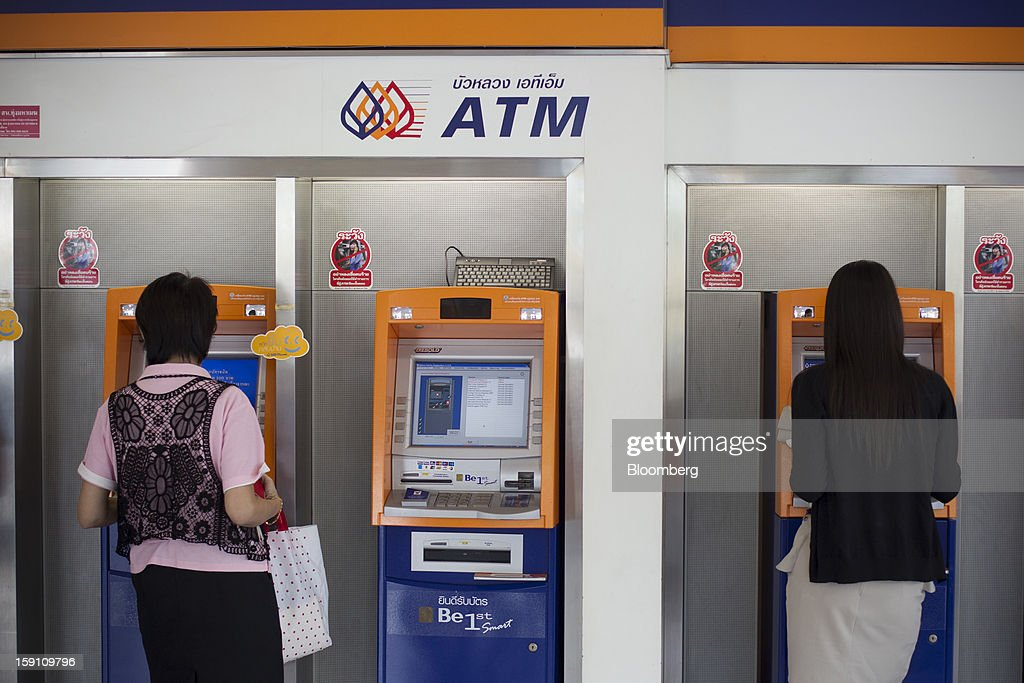 Customers use automated teller machines (ATM) at the Bangkok Bank Pcl. headquarters in Bangkok, Thailand, on Tuesday, Jan. 8, 2013. Thailand's economy may have expanded 5.7 percent in 2012 and will grow 5 percent in 2013, the finance ministry said on Dec. 26. Photographer: Brent Lewin/Bloomberg via Getty Images