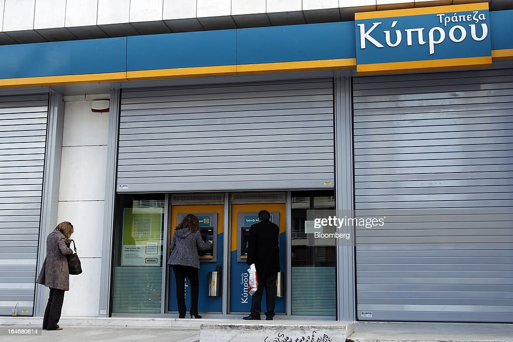 Customers use automated teller machines (ATM) beneath shutters outside a closed Bank of Cyprus Plc branch in Athens, Greece, on Tuesday, March 26, 2013. Piraeus Bank SA acquires Greek units of Cypriot lenders for total cash consideration of EU524m, according to e-mailed statement from the Athens-based lender today. Photographer: Kostas Tsironis/Bloomberg via Getty Images