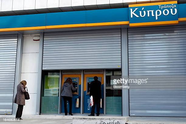 Customers use automated teller machines beneath shutters outside a closed Bank of Cyprus Plc branch in Athens Greece on Tuesday March 26 2013 Piraeus...