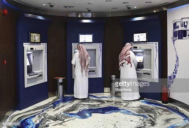Customers use automated teller machines inside the Al Rajhi Bank in Riyadh Saudi Arabia on Thursday Dec 1 2016 Saudi Arabia is working to reduce the...