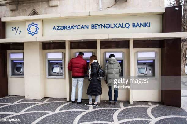 Customers use automated teller machines operated by the International Bank of Azerbaijan in Baku Azerbaijan on Friday March 16 2018 Azerbaijan's...