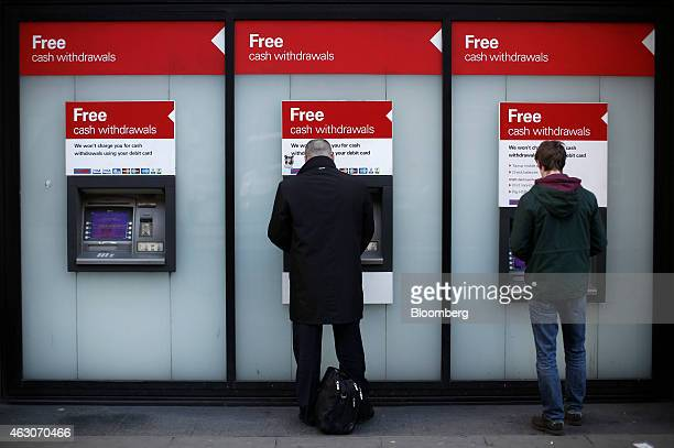 Customers use automated teller machines outside a bank branch, operated by HSBC Holdings Plc, in London, U.K., on Monday, Feb. 9, 2015. The...