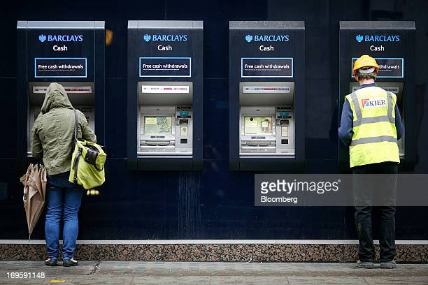Customers use automated teller machines outside a Barclays Plc bank branch in London UK on Tuesday May 28 2013 Britain's four biggest banks will have...