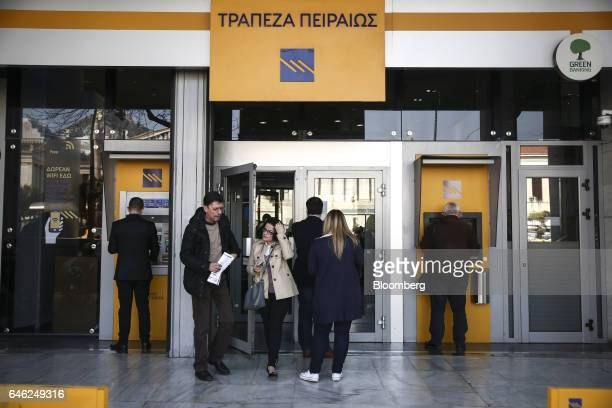 Customers use automated teller machines outside a Piraeus Bank SA bank branch in Athens Greece on Tuesday Feb 28 2017 Greeces auditors are pulling...
