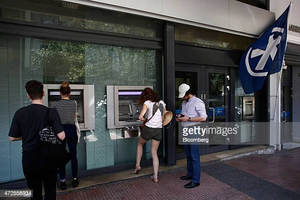 Customers use automated teller machines outside an Alpha Bank AE bank branch in Athens Greece on Friday May 8 2015 Prime Minister Alexis Tsipras said...