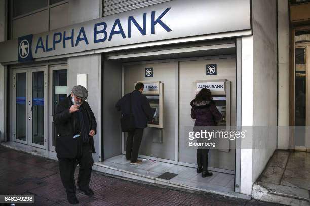 Customers use automated teller machines outside an Alpha Bank AE bank branch in Athens Greece on Tuesday Feb 28 2017 Greeces auditors are pulling...