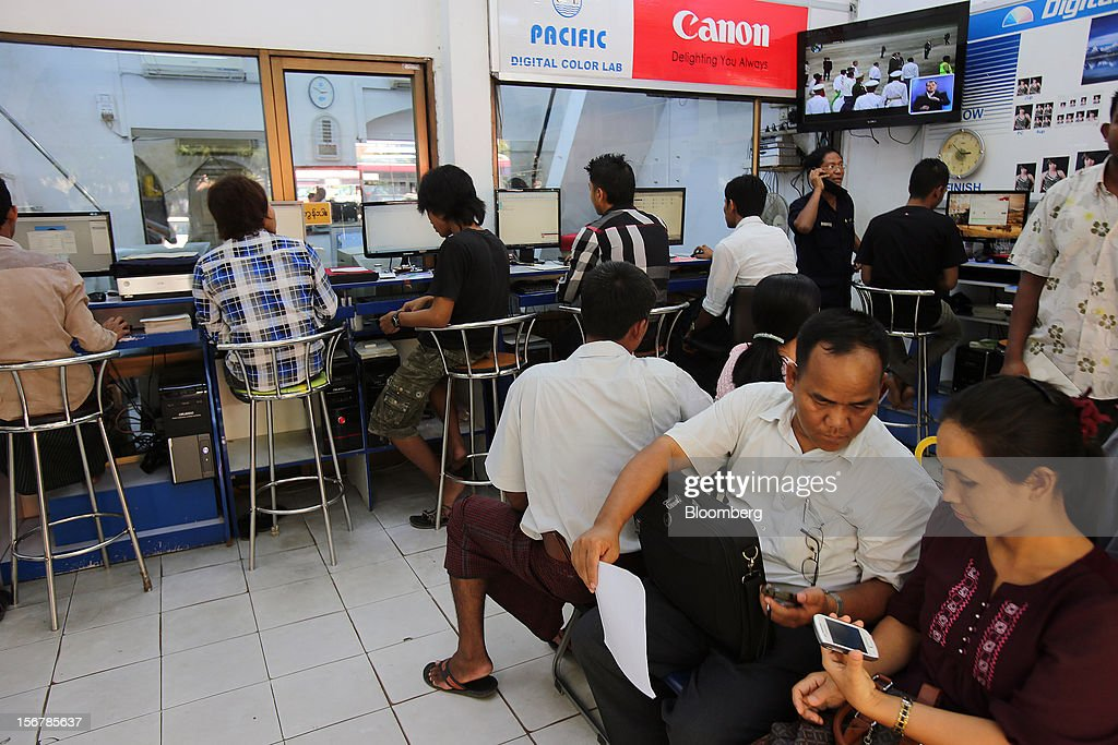 Customers use computers and mobile phones at an internet and multimedia services store in Yangon, Myanmar, on Tuesday, Nov. 20, 2012. Myanmar's growth outlook has improved 'substantially' amid political reforms, which are expected to lead to a large influx of foreign investment, the Organization for Economic Cooperation and Development (OECD) said on Nov. 18. Photographer: Dario Pignatelli/Bloomberg via Getty Images