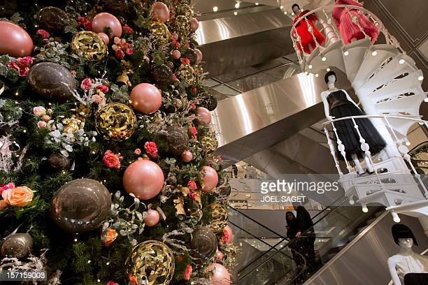 Customers use escalators above christmas decorations on November 28 in Paris at the Printemps department store AFP PHOTO JOEL SAGET