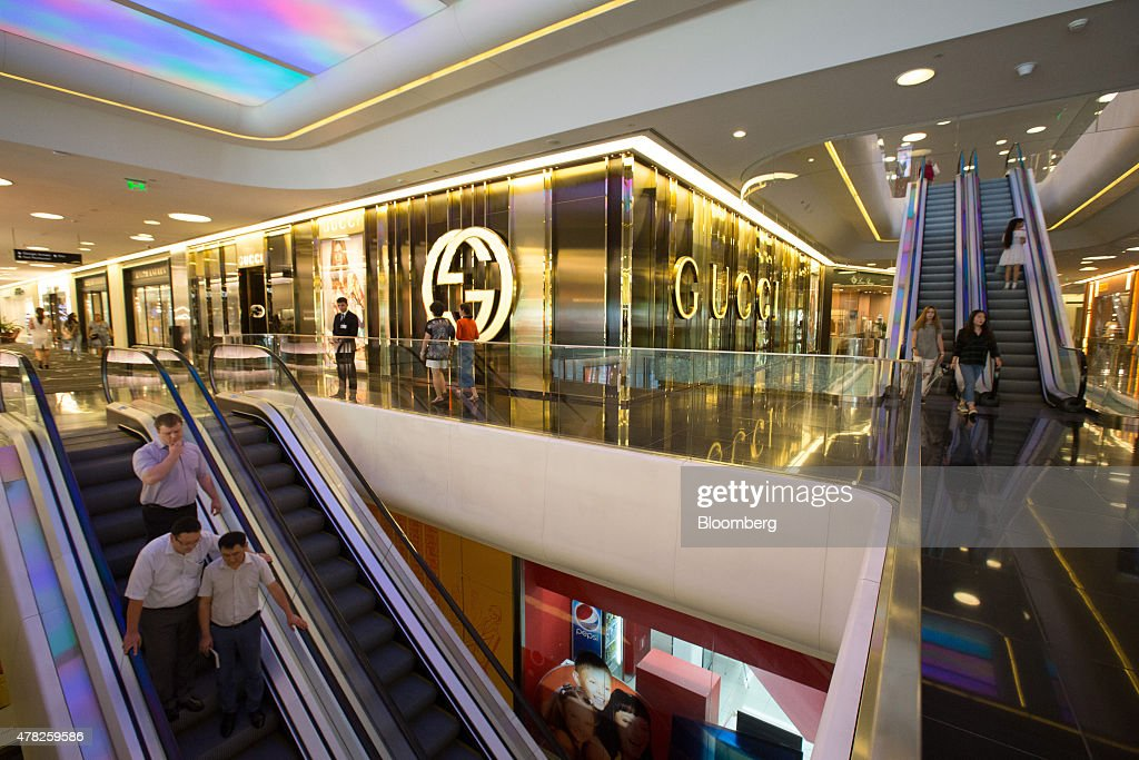 Customers use escalators to move between shopping floors near a Gucci fashion store, operated by Kering SA, at the Esentai luxury shopping mall in Almaty, Kazakhstan, on Tuesday, June 23, 2015. Kazakhstan completed its negotiations to become the 162nd member of the World Trade Organization, after 19 years of negotiations, and hopes to fully ratify its accession by Oct. 31. Photographer: Andrey Rudakov/Bloomberg via Getty Images